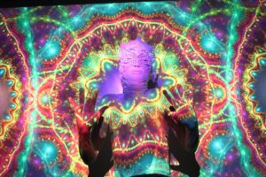 A person wearing an ornate mask standing with hands up as a bright and colourful design is projected onto them.