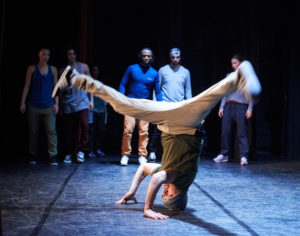A breakdancing performer doing a headstand with legs spread in the air.