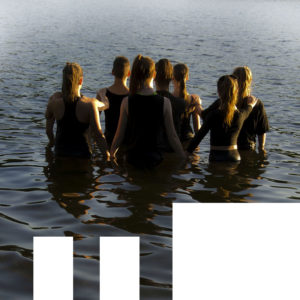7 people standing in the water with backs to the camera.
