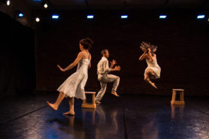 3 dancers performing. One is jump into the air. The other 2 have 1 leg raised.