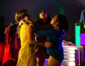 3 performers standing in a circle with arms on each others shoulders.
