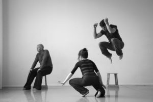 3 dancers performing. One is jumping into the air.