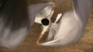 A bird's eye view of a person dancing in a long robe.