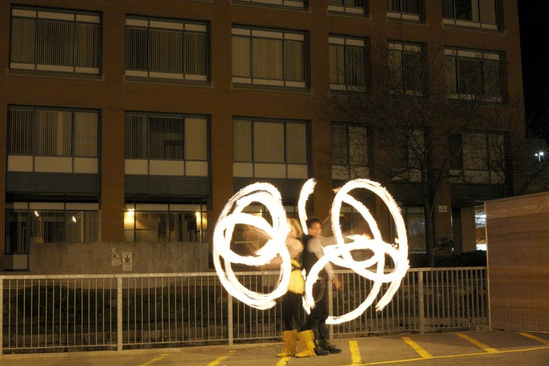 2 people, back to back, performing fire spining (Poi) in a parking lot.