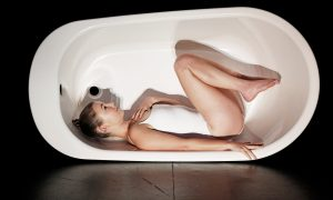 Nora Sadava performing in a bathtub.