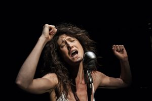 Amy Nostbakken performing in front of a microphone with arms raised.