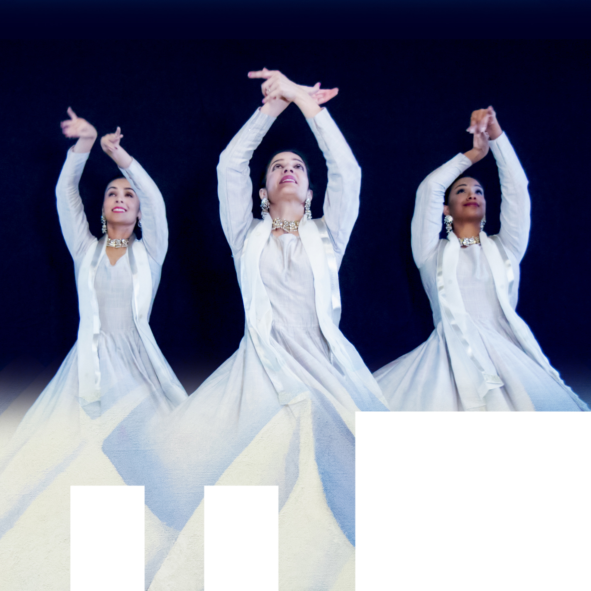 3 dancers in white robes with arms raised.