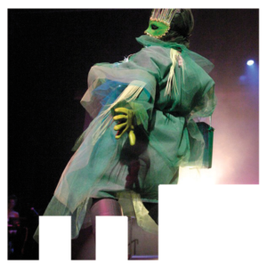 A model at the Wearable Artshow in a ruffled green sheer robe with matching mask and gloves.