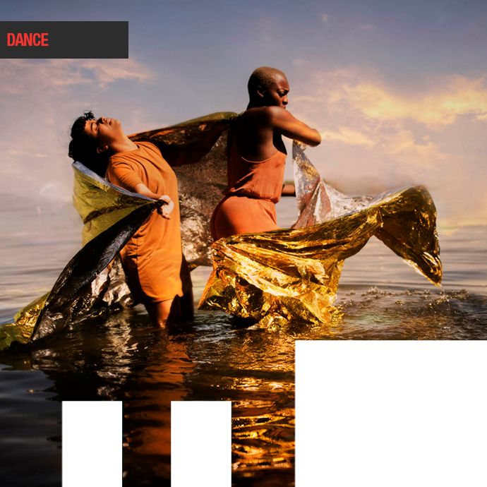 No Woman's Land (World Premiere) Two African- Canadian Dancers in a lake knee high. a gold flowing sheet is flown around them. in the photo.
