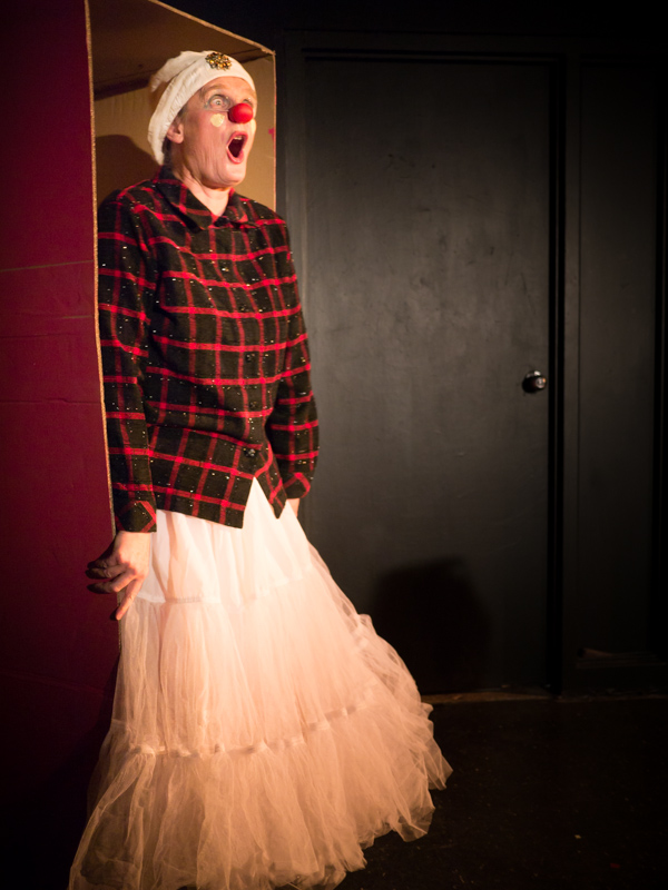A clown wearing a red and black plaid shirt and a frilly skirt.