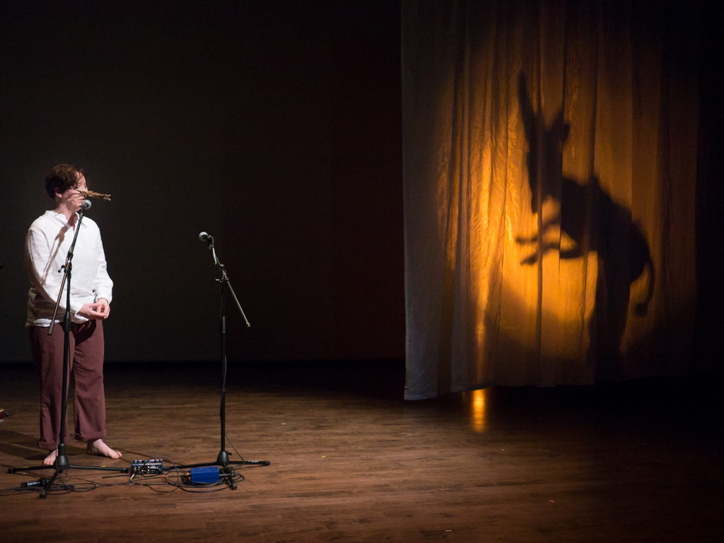 A person performing on stage. The their left in shadow on the curtain appears to be a monster.