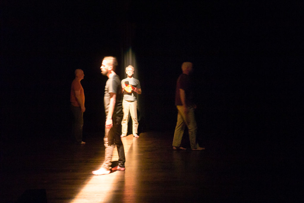 4 performing on a dimly lit stage. A shaft of light casts down the middle.