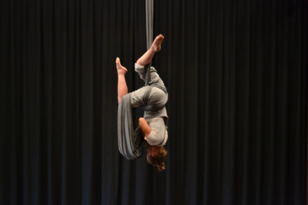 Nicole Malbeuf hanging from silk upside down.