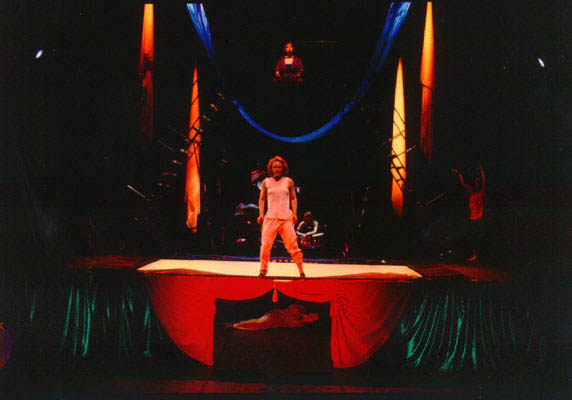 A man stands on stage with a defiant stance. Beneath the stage someone lies on their side, hiding. Above the stage sits a man in a robe, dramatically lit.