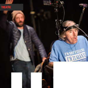 Two actors, one faded into the background and the second actor is in the front in a chair with a electronic headpiece on.