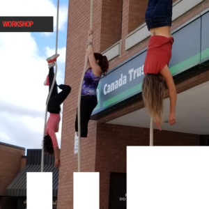 Three female aerial performers hang from the side of Peterborough Square.