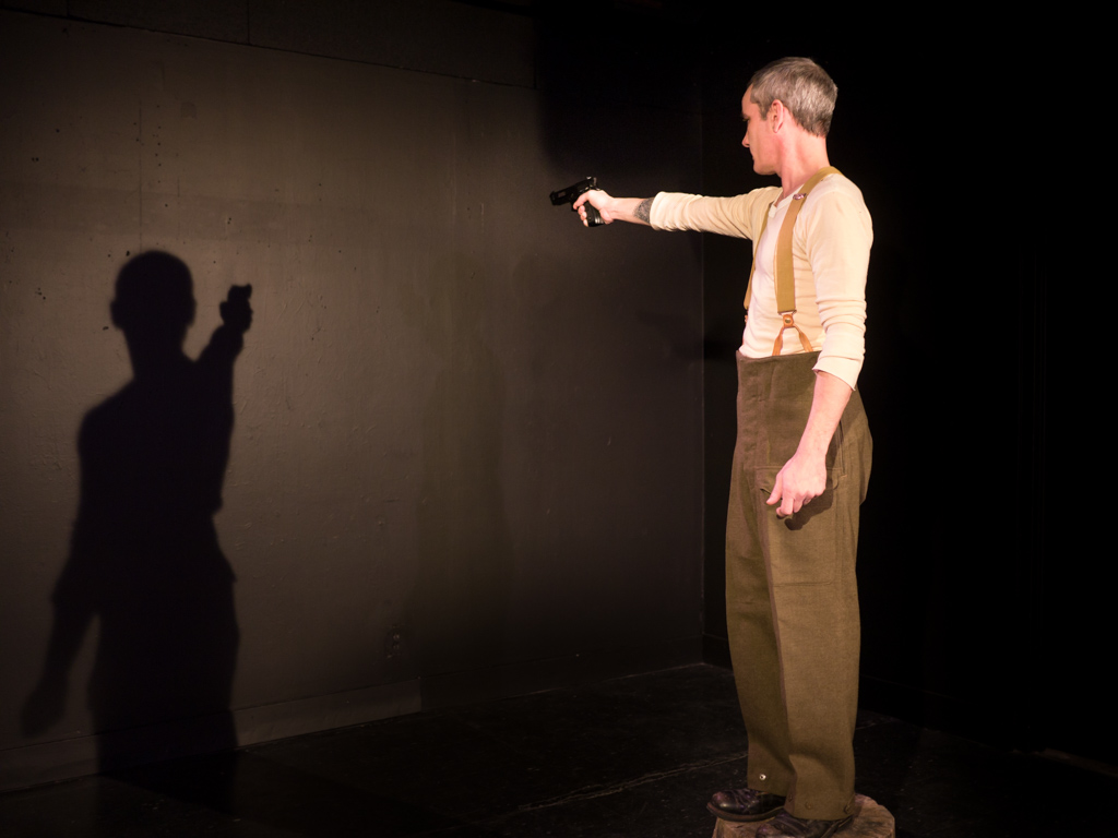 Performer Ryan Kerr, dressed in military slacks, stands on a stool aiming a gun at his shadow on the black wall