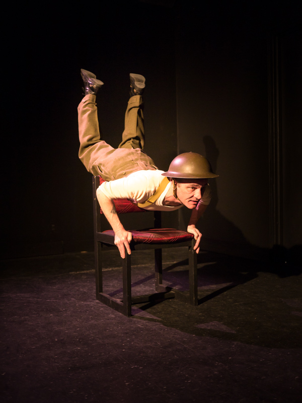 Performer Ryan Kerr balances on a chair with his torso parallel to the ground and his feet in the air, emulating the pose of a parachute jumper mid flight. He wears a WW1 helmet, military slacks and combat boots