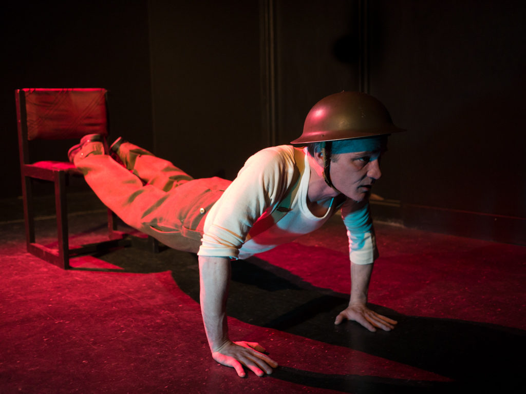 Performer Ryan Kerr poses as if doing push ups with his feet balanced on a chair behind him. He wears a military helmet and military slacks. The room is cast in red light.