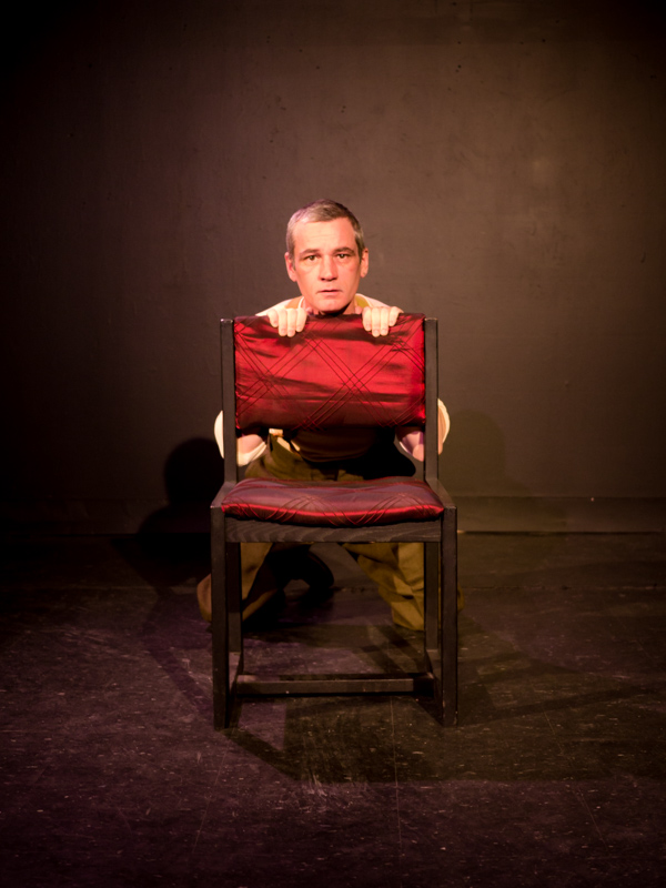 Performer Ryan Kerr crouches behind a red chair. His face is exposed and he stares at the camera.