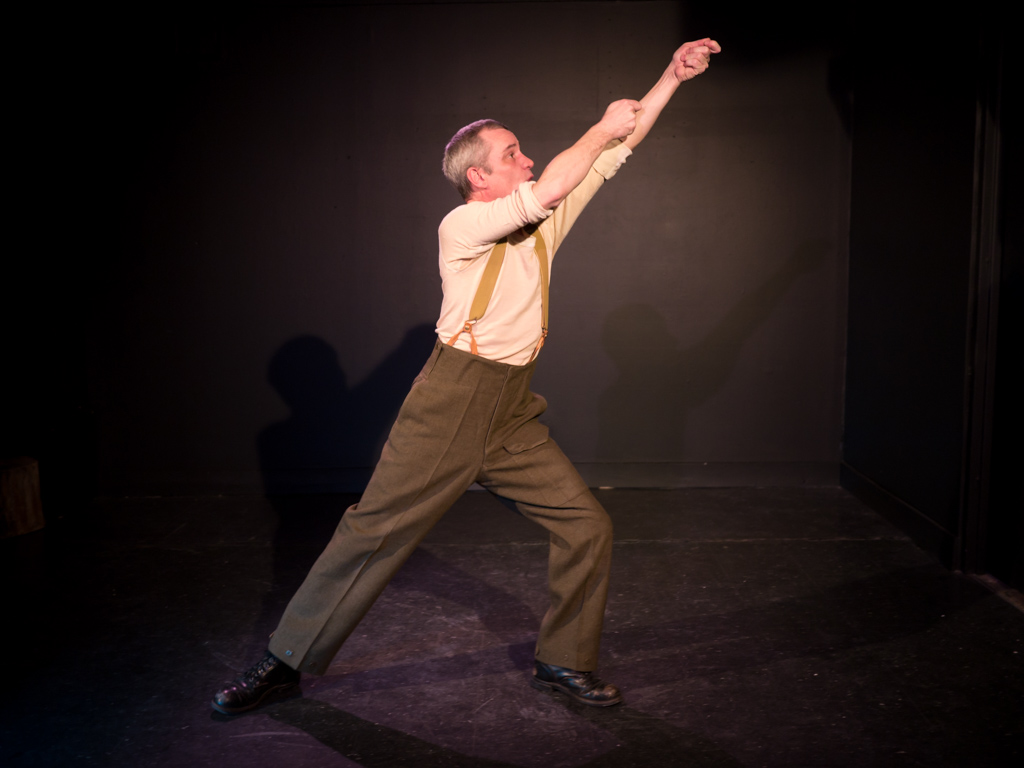 Performer Ryan Kerr, dressed in combat boots and military slacks, lifts his arms in the air with his hands appearing to make a hoisting motion