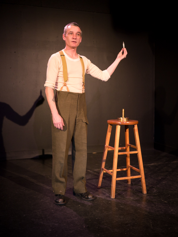 Performer Ryan Kerr, in military garb, holds up a metal bullet casing. He stands beside a wooden stool