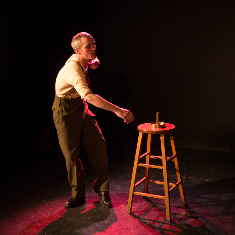 Performer Ryan Kerr, dressed in military garb, appears to recoil and lose his balance. He reaches for the wooden stool beside him, which has a round metal object on it