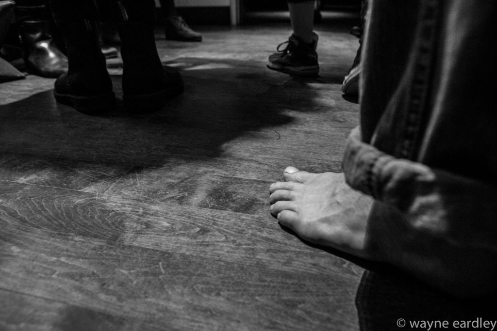 Bare feet of audience on Market Hall floor. In Greyscale.