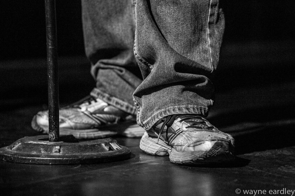 Bill Kimball's sneakers during Public Energy's 25th Anniversary Mainstage event. In greyscale.
