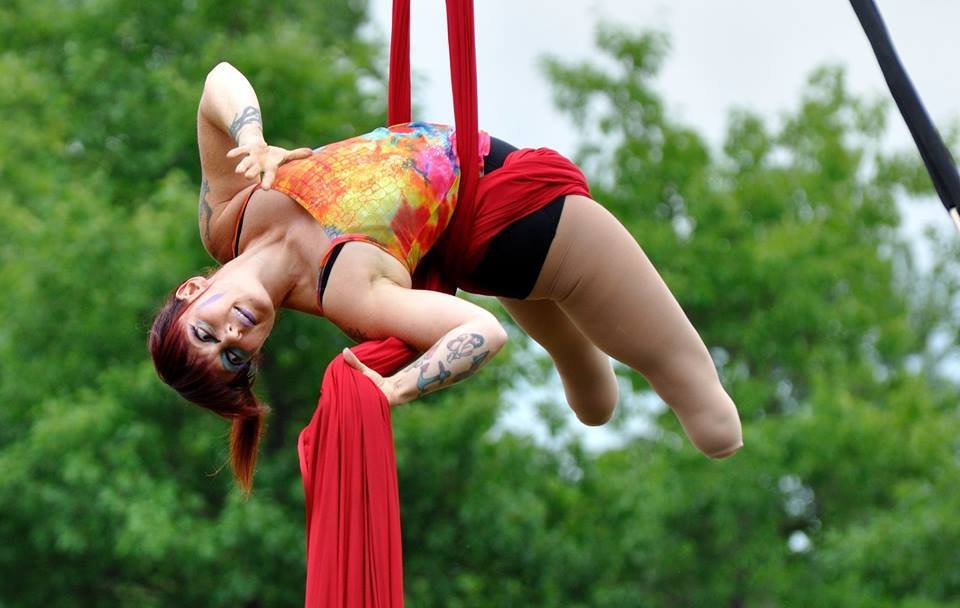 Erin Ball performs outside on red aerial silks.