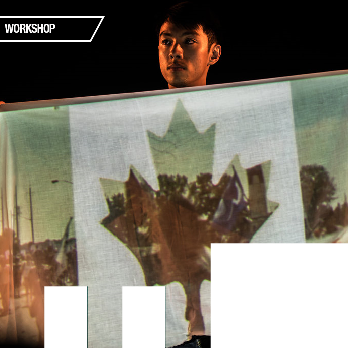 <em>Devised Theatre Workshop: Objects and Personal Storytelling</em>, Kevin Matthew Wong, Broadleaf Theatre Kevin Matthew Wong hols a piece of fabric, onto which is projected a Canadian glaf with photos of protesters replacing the red portion of the flag in the photo.