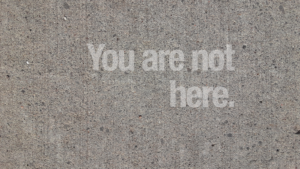 "The words ""You Are Not Here"" appear translucent over concrete."