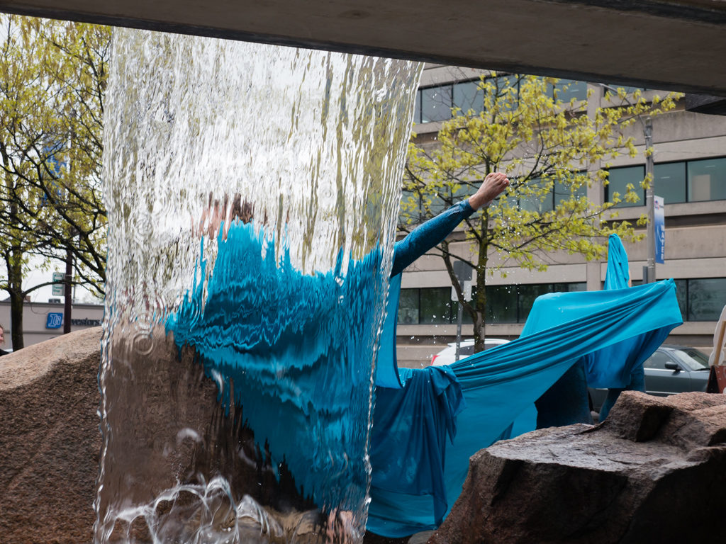 Photo of a waterfall with people huddled under a blue silk in front