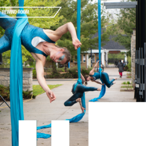 Three women perform in blue sparkling leotards on aerial silks suspended in a city park