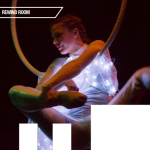 A woman suspends from an aerial hoop, her arms hooked over the hoop. She wears a dress fabricated with white fairy lights within the fabric.