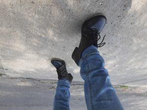 Tap dancing feet on a concrete sidewalk.