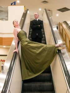 Kate Story and Ryan Kerr on an escalator in a shopping mall.
