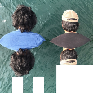 Two heads seen from behind and reflected in water.