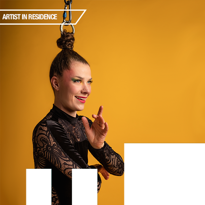 Nicole Malbeuf suspended by her hair on a yellow background.