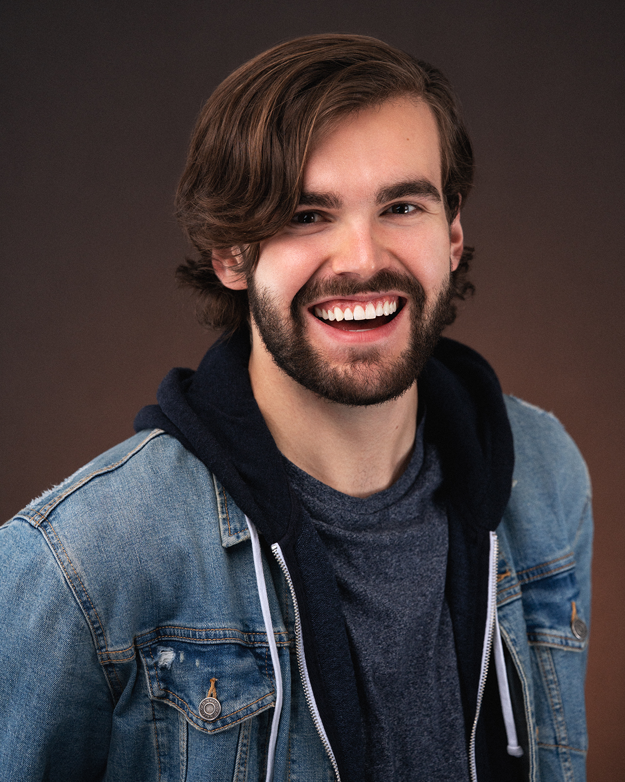 Headshot of Noah Sisson in a jean jacket, smiling.
