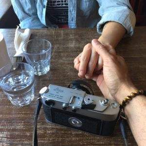 photo of two people at a table on holding the other's hand. a camera on drinking glasses and cutlery are on the table.