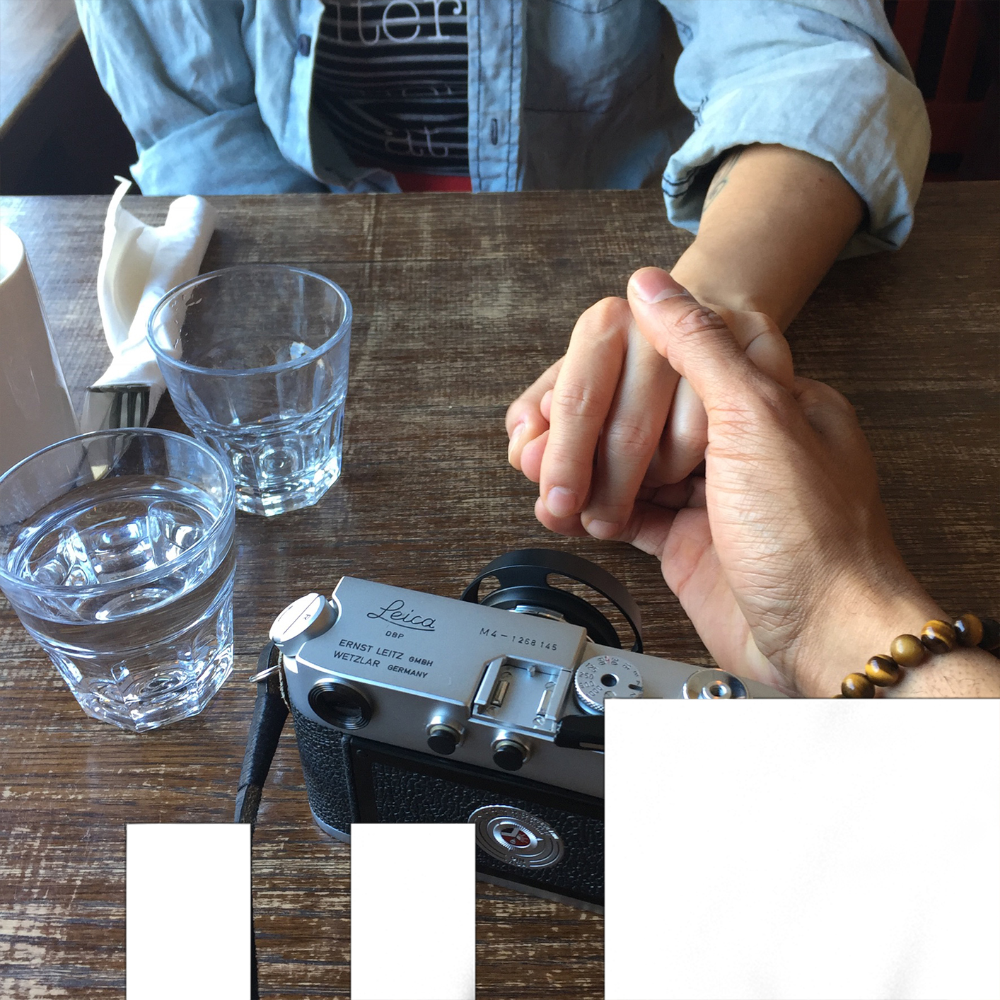 Bridge Over Troubled Water photo of two people at a table on holding the other's hand. a camera on drinking glasses and cutlery are on the table. in the photo.