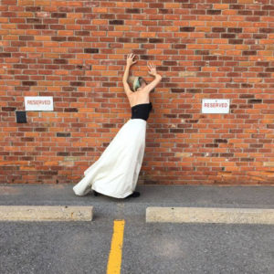 photo shot from behind of Kate Story with her hand on a brick wall in a parking lot