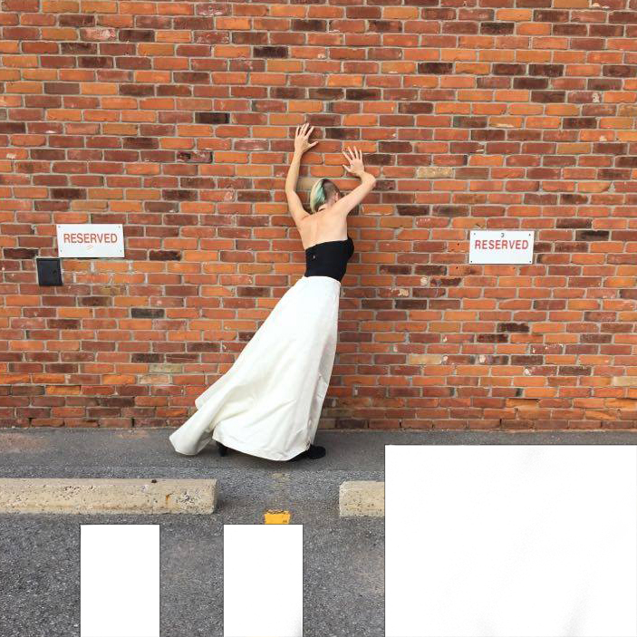Love in the Time of Covid photo shot from behind of Kate Story with her hand on a brick wall in a parking lot in the photo.