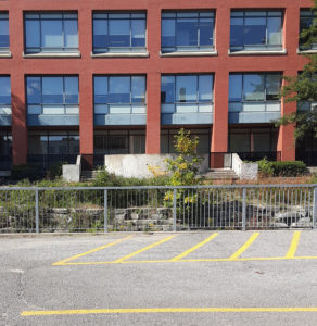 red brick build office building with many windows and a parking lot in front