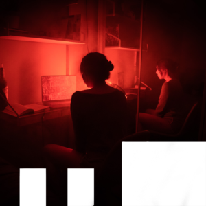 A woman sitting at a computer in the dark.
